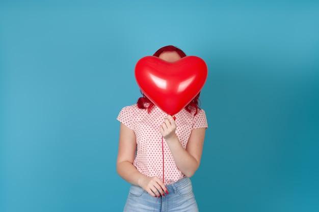 심장의 형태로 빨간 비행 풍선 뒤에 숨어있는 빨간 머리를 가진 여자