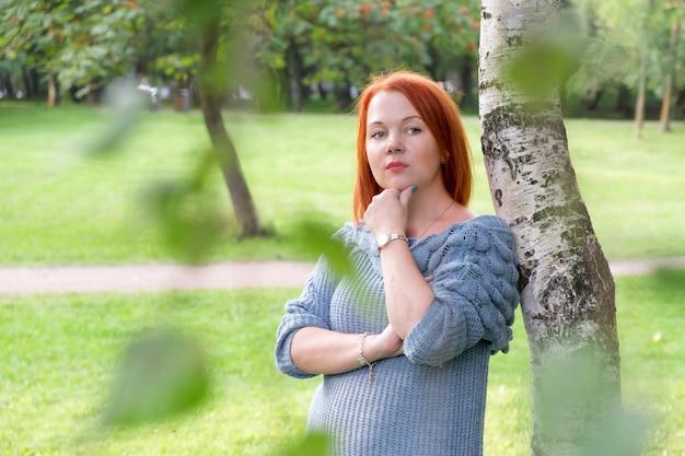 파란색 니트 스웨터에 빨간 머리를 한 여자는 자작나무 옆에 서서 옆을 생각에 잠겨 봅니다