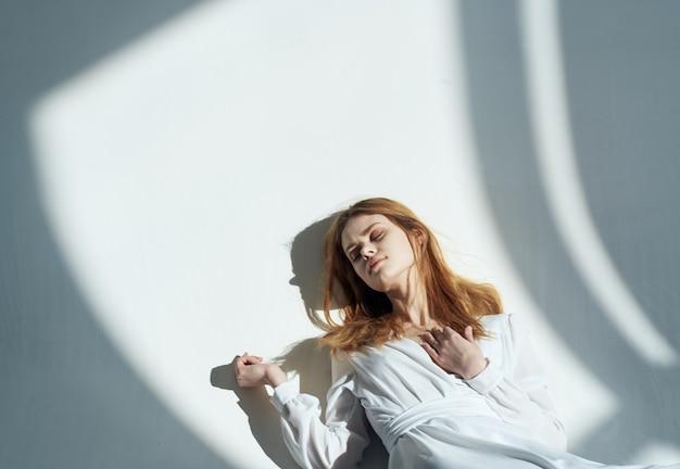 北の壁にもたれて赤い髪と落ちてくる影の女性