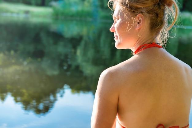 Женщина с рыжими волосами на озере