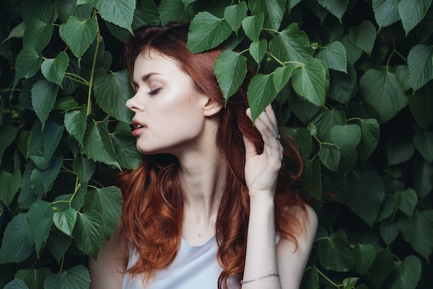 Woman with red hair posing among green leaves