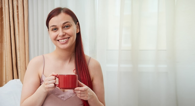 赤い髪の女性は、コピースペースと朝のコーヒーバナーのカップとウィンドウの背景に座っています