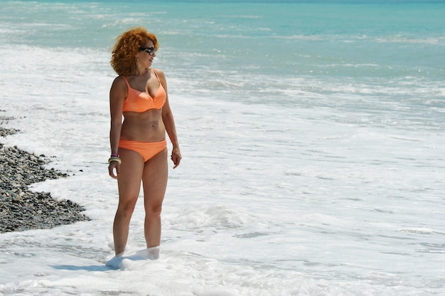 Woman with red hair in sunglasses and an orange swimsuit