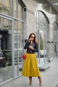 비즈니스 빌딩 근처에 전화로 말하는 동안 걷는 빨간 핸드백을 가진 여자