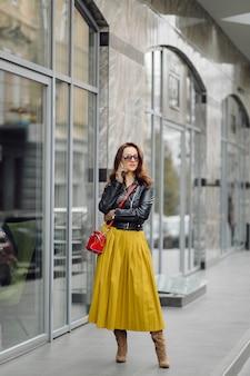 ビジネスビルの近くで電話で話している間歩いている赤いハンドバッグを持つ女性