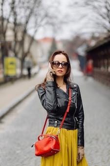 電話で話している間歩いている赤いハンドバッグを持つ女性
