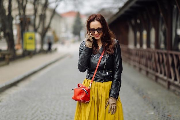 전화로 말하는 동안 걷는 빨간 핸드백을 가진 여자