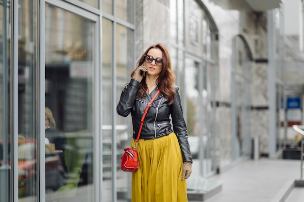 Woman with red handbag walking while speaking on the phone near a business building