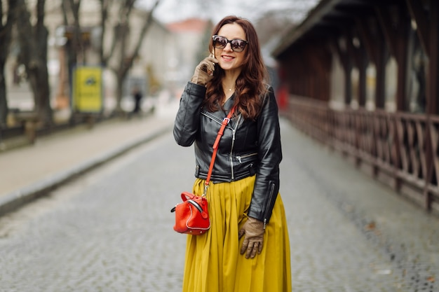 Woman with red handbag walking while speaking on the phone
