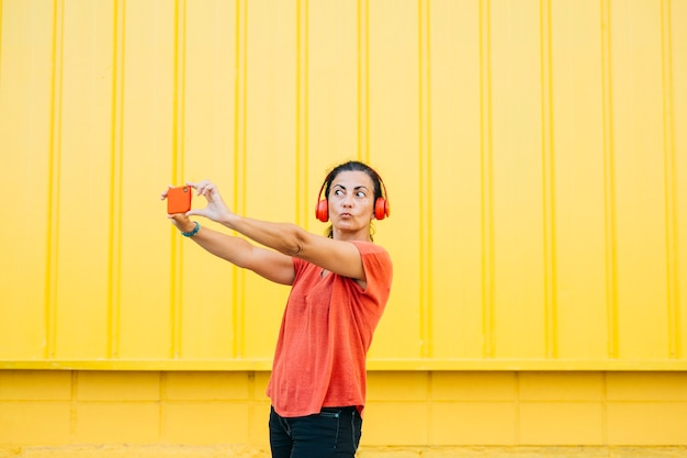 Woman with red headphones and taking a selfie against a yellow background