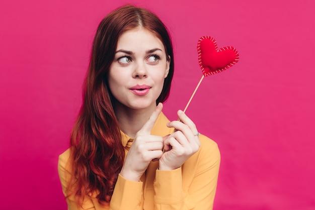 スティックとピンクの背景に生地で作られた赤いハートの女性バレンタインデー