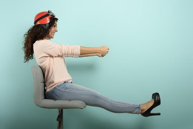 赤いヘルメットをかぶった女性は速い車を運転しようと考えています。シアンの壁。
