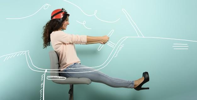 赤いヘルメットをかぶった女性は速い車を運転しようと考えています。