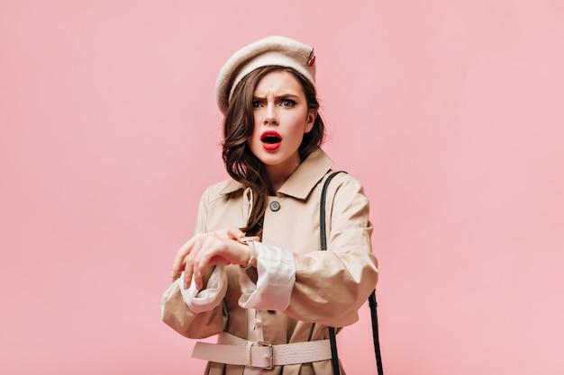赤い唇と緑の目を持つ女性は、カメラを憤慨して見ています。フェルトの帽子と塹壕を身に着けている女の子の肖像画。
