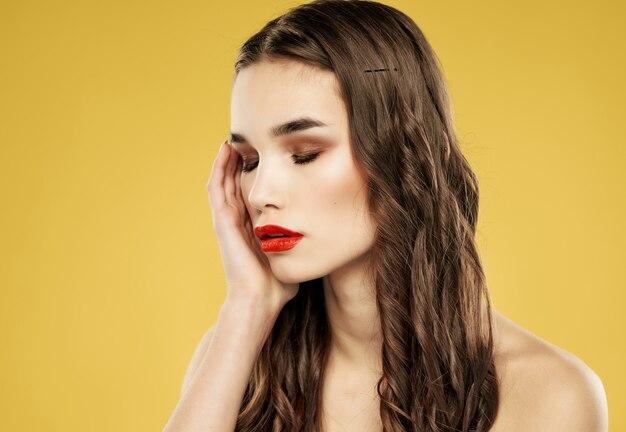 Женщина с красными губами прическа мода заделывают желтый фон
