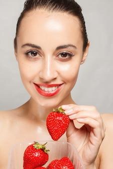딸기의 전체 플라스틱 용기를 들고 붉은 입술을 가진 여자
