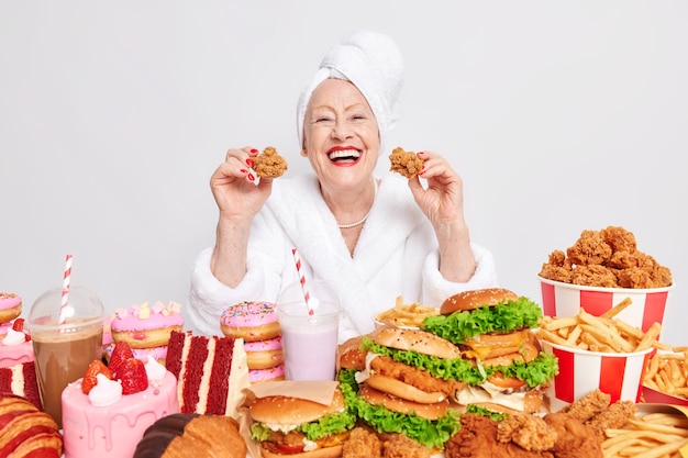Woman with red lips holds two nuggets eats cheat meal dressed in bathrobe surrounded by unhealthy food on white