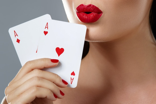 Woman with red lips is holding two aces.