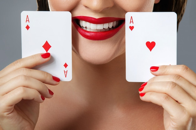 赤い唇を持つ女性は2つのエースを保持しています。