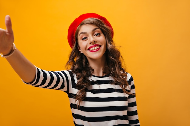 웃 고 격리 된 배경에 selfie를 만드는 붉은 입술을 가진 여자. 줄무늬 스웨터와 빨간 베레모 포즈에 물결 모양의 머리를 가진 즐거운 소녀.