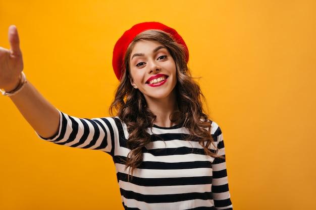 Donna con le labbra rosse che sorride e che fa selfie su priorità bassa isolata. ragazza allegra con capelli ondulati in maglioni a righe e berretto rosso in posa.