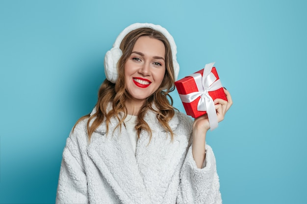 赤い贈り物を保持している赤い口紅を持つ女性