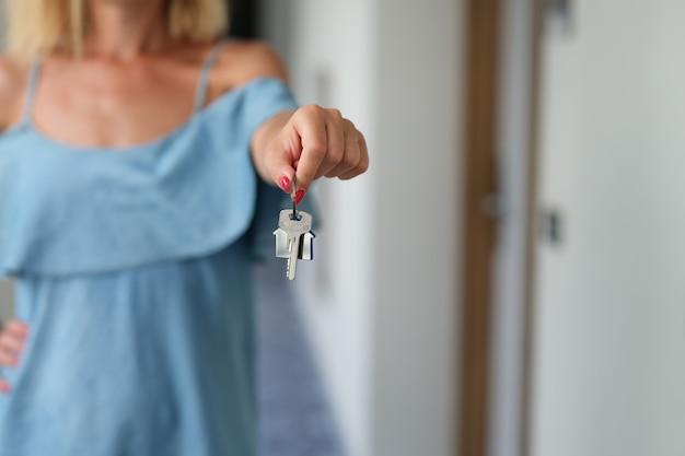 彼女の手のクローズアップでアパートの鍵を保持している赤いマニキュアを持つ女性