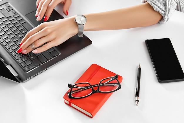 집에서 흰색 테이블 비즈니스 여자 작업에 노트북과 빨간 매니큐어 작업을 가진 여자