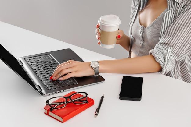 집에서 화이트 테이블 비즈니스 여자 작업에 노트북과 빨간 매니큐어 작업을 가진 여자