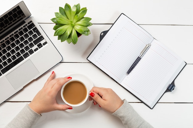 Woman with red nails holding cup of coffee near modern laptop, plant pot and notebook with pen.