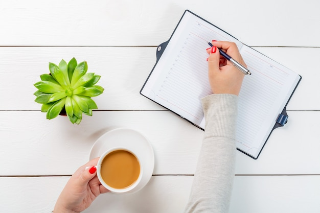 Woman with red nails holding cup of coffee and writing with a pen in a notebook organiser near plant pot on white wooden table.