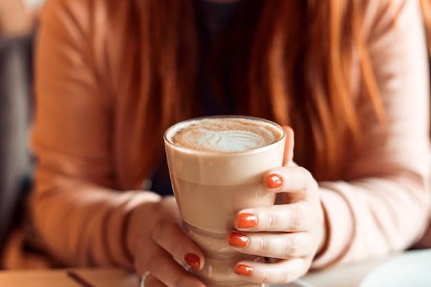 Женщина с красными ногтями сидит и держит чашку горячего кофе. крупным планом руки с латте, красный маникюр
