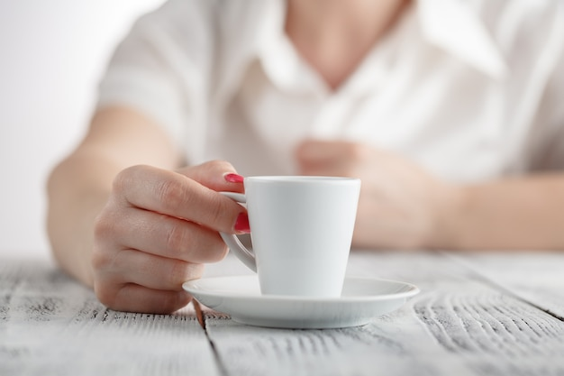 Woman with red nails sitting and holding a hot cup of coffee
