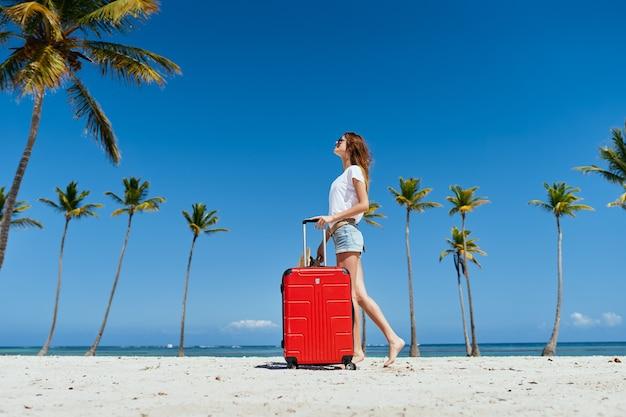 ヤシの島の赤いスーツケースを持つ女性は新鮮な空気を旅行します