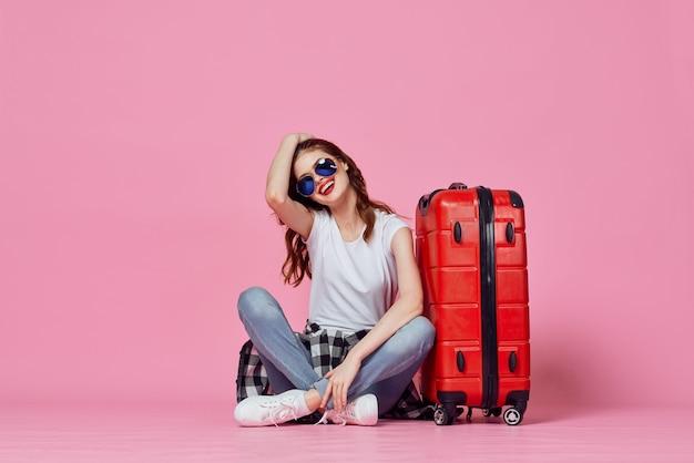 赤いスーツケースのパスポートと飛行機のチケット旅行ピンクの背景を持つ女性