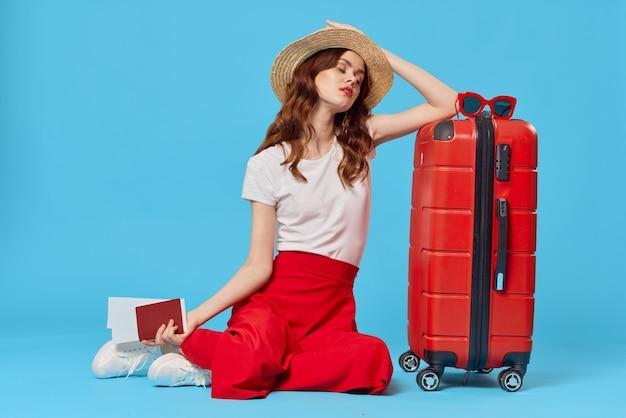 床に座っている赤いスーツケースを持つ女性青い背景旅行休暇