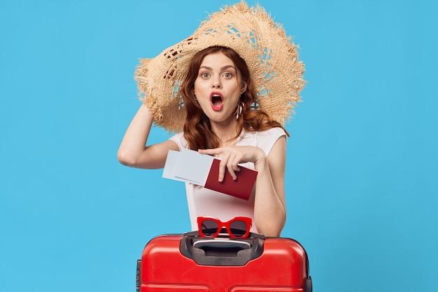 바닥 파란색 배경 여행 휴가에 앉아 빨간 가방을 가진 여자