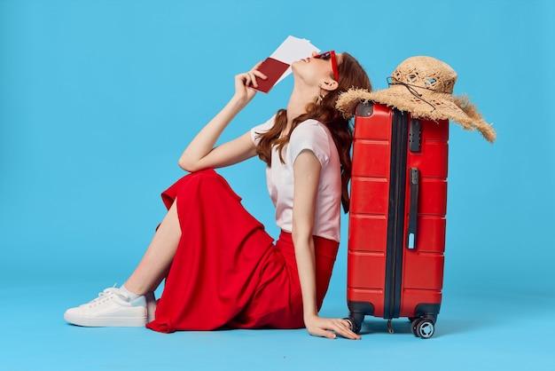 Женщина с красным чемоданом сидит на полу паспорта билетов на самолет путешествует на синем фоне