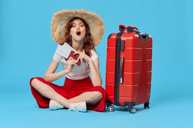 床のパスポートと飛行機のチケットのライフスタイルに座っている赤いスーツケースを持つ女性
