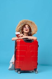Женщина с красным чемоданом сидит на полу в паспорте и билетах на самолет