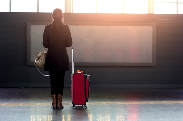 Woman with red suitcase standing in airport on front of flight timetable