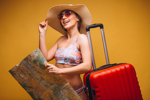 Woman with red suitcase and travelling map in a swimming suit isolated