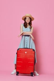 旅行の予定の孤立した背景の代わりに赤いスーツケースの休暇を持つ女性