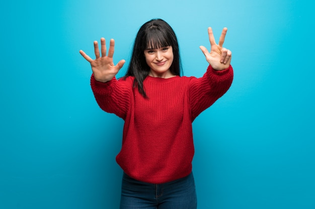 Woman with red sweater over blue wall counting eight with fingers