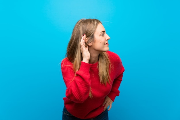 Woman with red sweater over blue wall listening to something by putting hand on the ear