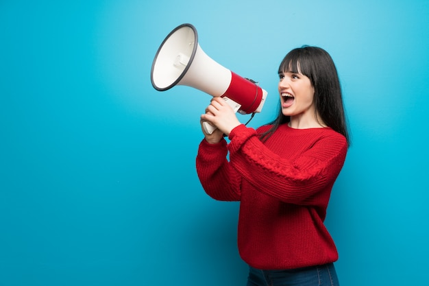 Woman with red sweater over blue wall shouting through a megaphone