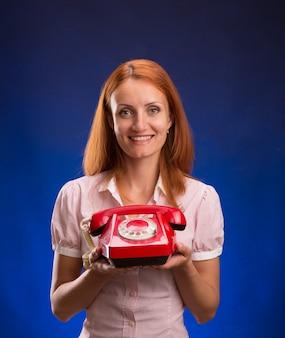 赤い電話を持つ女性
