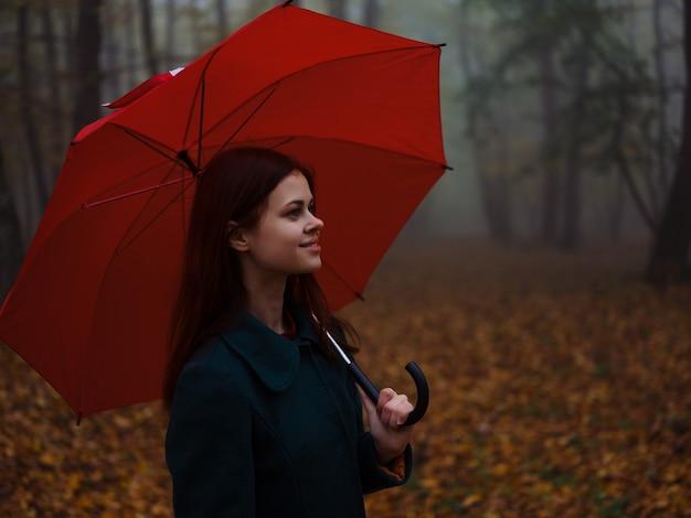 赤い傘のコート秋の森の霧の性質を持つ女性