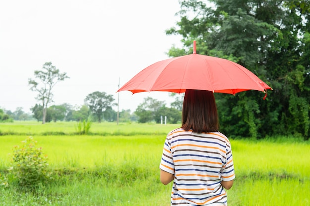 Woman with red umbrella and green rice fields.