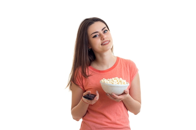 Woman with remote control from the tv and popcorn in the hands isolated on white